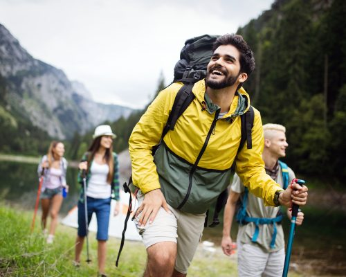 Group of young friends hiking in countryside. Multiracial happy people traveling in nature