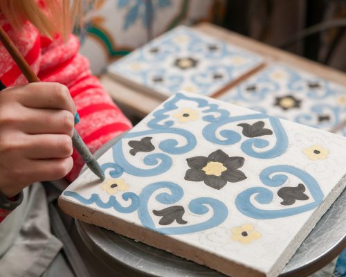 A pottery decorator painting a ceramic tile with floral motifs in his work table in Caltagirone, Sicily