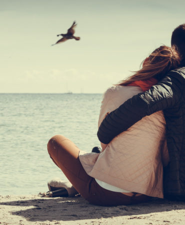 loving couple spending leisure time together at beach hugging rear view